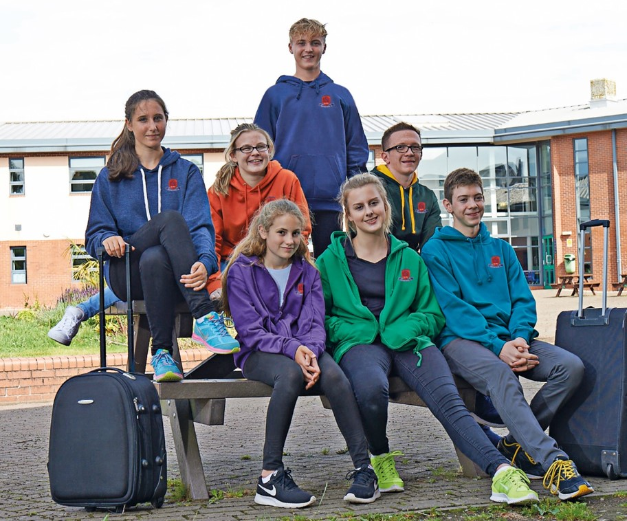 Teenagers wearing a selection of different hoodies for a school trip